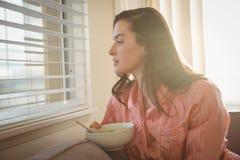 Женщина смотря через окно пока сидящ на софе Стоковое Фото