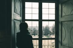 Женщина смотря через окно, тонизированное изображение, винтажный стиль Городской пейзаж Турина, Турин, Италия, старый дом, вид сз стоковая фотография rf