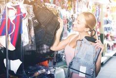 Женщина смотря через различные одежды для собаки Стоковое Изображение RF
