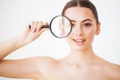 Женщина смотря через увеличитель и усмехаясь близко вверх стоковое фото rf