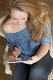 Женщина смотря экран таблетки компьютера Стоковое Изображение
