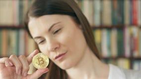 Женщина смотря bitcoin cryptocurrency Сияющие виртуальные деньги онлайн торговли Фокус на bitcoin видеоматериал