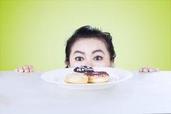 Женщина смотря donuts на таблице Стоковое фото RF