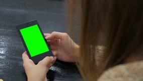 Женщина смотря smartphone с зеленым экраном Стоковое фото RF
