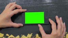 Женщина смотря smartphone с зеленым экраном Стоковые Изображения