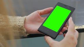 Женщина смотря smartphone с зеленым экраном Стоковые Изображения RF