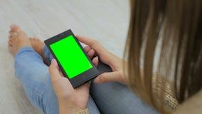 Женщина смотря smartphone с зеленым экраном Стоковое Изображение