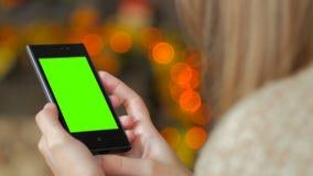Женщина смотря smartphone с зеленым экраном Стоковые Фотографии RF