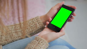 Женщина смотря smartphone с зеленым экраном Стоковая Фотография RF