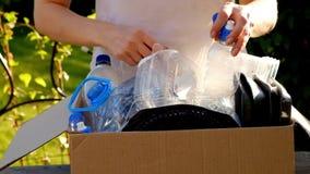 Женщина собирая пластичные бутылки и контейнеры для рециркулировать акции видеоматериалы