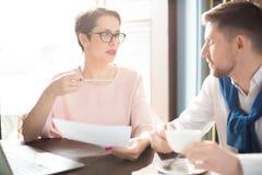 Женщина советуя с с человеком о бумагах Стоковое Изображение
