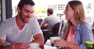 Женщина соединяет человека сидя на таблице в кофейне акции видеоматериалы