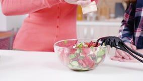 Женщина соля салат на кухне видеоматериал