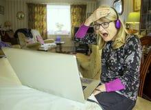 Женщина, сотрясенная на онлайн материале она осматривает стоковое фото rf