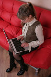 женщина софы компьтер-книжки стекел красная Стоковое Фото