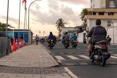 Женщина со скутером в мужчине, Мальдивах стоковое изображение