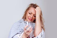 Женщина со стеклянной чувствуя головной болью стоковые фото