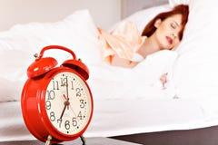 Женщина спать на белых постельных бельях в кровати дома стоковые изображения