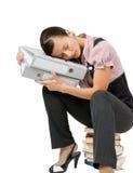 Женщина спать на книгах работник офиса утомленный стоковое фото