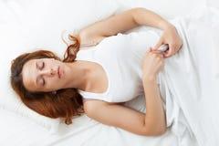 Женщина спать на пушистой подушке в кровати дома Стоковое фото RF