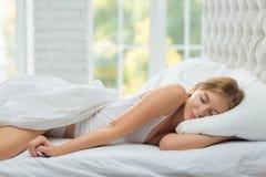 Женщина спит на белой кровати Стоковое Изображение