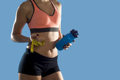 Женщина спорта держа abs и живот показа бутылки с водой и ленты измерения тонкий совершенный Стоковое фото RF