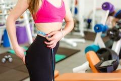 Женщина спортзала принимая измерения с рулеткой Стоковое Изображение