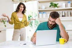 Женщина споря с человеком осадки в кухне Стоковое Изображение