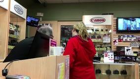 Женщина спрашивая новое цену камеры на магазине камер Kerrisdale сток-видео