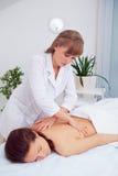 Женщина спы Женщина наслаждаясь ослабляющ задний массаж в центре курорта косметологии Забота тела, забота кожи, здоровье, благопо Стоковые Фотографии RF