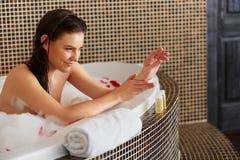 Женщина спы Красивая женщина в заботах ванны о ее руках Тело c Стоковые Изображения