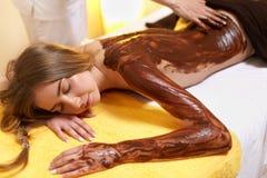 Женщина спы Молодая женщина получает маску тела шоколада на салоне красоты стоковая фотография