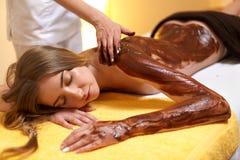 Женщина спы Молодая женщина получает маску тела шоколада на салоне красоты стоковая фотография rf