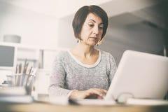 Женщина среднего возраста используя computerpt стоковые изображения rf