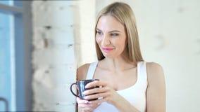 Женщина среднего конца-вверх задумчивая молодая европейская смотря на окне на белом интерьере просторной квартиры видеоматериал