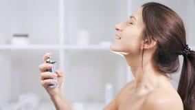 Женщина среднего конца-вверх нагая красивая усмехаясь и брызгает духи на замедленном движении шеи видеоматериал