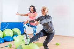Женщина средн-постаретая Active разрабатывая при шарик стабильности принимать класс фитнеса группы стоковое изображение