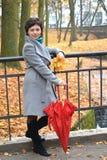 Женщина средних лет держит красный зонтик в парке осени Стоковое фото RF