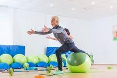 Женщина средн-постаретая Active разрабатывая при шарик стабильности принимать класс фитнеса группы стоковые изображения rf
