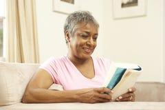 женщина старшия чтения книги домашняя Стоковая Фотография