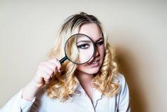женщина стеклянного удерживания увеличивая стоковое фото rf