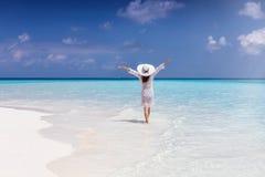 Женщина стоит в бесконечном море бирюзы на солнечный день стоковое изображение rf