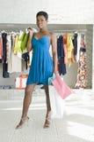 Женщина стоит в магазине одежд с хозяйственными сумками Стоковое Изображение