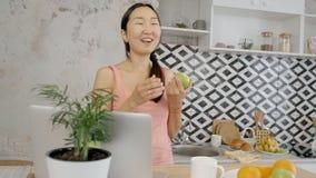 Женщина стоит на кухне, смеется и беседуется ноутбуком акции видеоматериалы