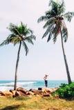 Женщина стоит на побережье океана и смотрит на линии horizont Стоковая Фотография