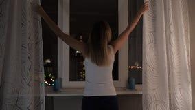 Женщина стоит на Windows на ноче смотря уличные светы, занавесы стоковые фото