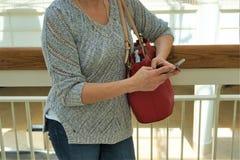 Женщина стоит получившей SMS по телефону стоковое изображение