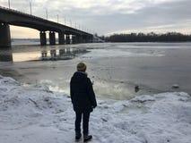 Женщина стоит рядом с мостом над замороженным рекой на заходе солнца стоковые фотографии rf