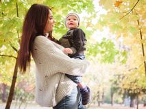 Женщина, стойки в осени паркует и владения на руках смотря ее маленького сына Концепция семьи стоковое изображение rf
