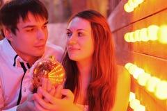 женщина стойки человека владением рождества шарика Стоковые Изображения RF